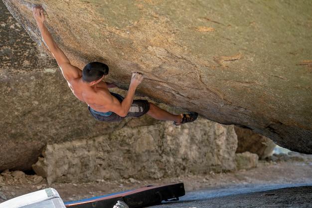 Młody i silny alpinista uprawiający wspinaczkę