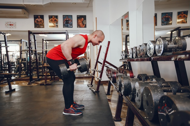 Młody i silny facet trenuje na siłowni