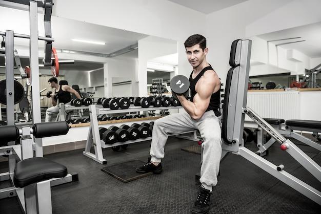 Młody i sprawny mężczyzna trenuje w siłowni