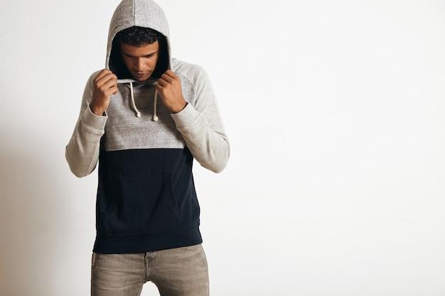 Młody i sprawny mężczyzna w pustym szarym czarnym swetrze z kapturem pozuje przed białą ścianą, patrząc w dół