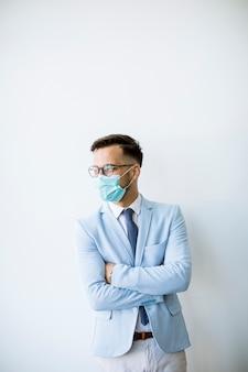 Młody i stylowy biznesmen z maską stoi przy ścianie w biurze