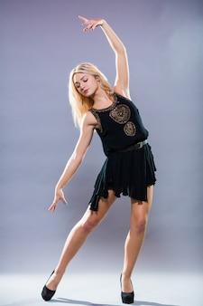 Młody i stylowy tancerz pozowanie na szarym tle