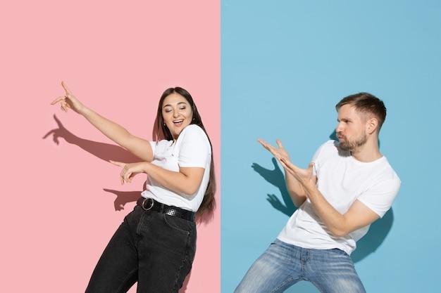 Młody i szczęśliwy mężczyzna i kobieta w zwykłych ubraniach na różowej, niebieskiej dwukolorowej ścianie, taniec