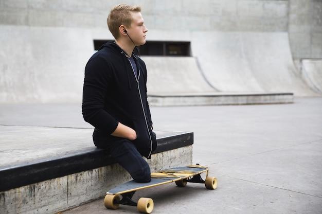 Młody i zmotywowany niepełnosprawny facet z longboardem w skateparku