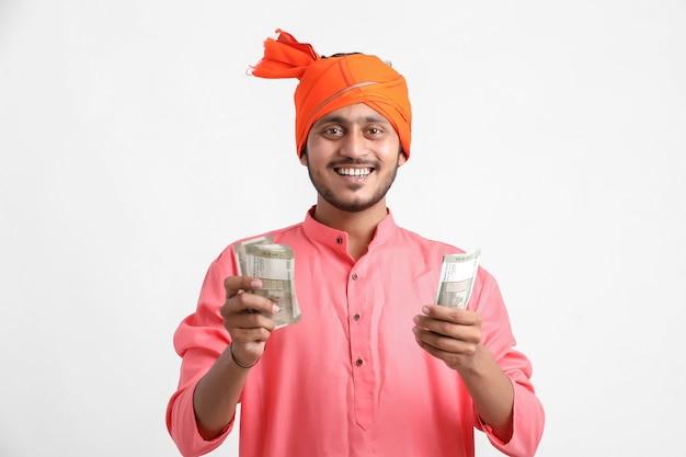 Młody indianin pozowanie z walutą na białej ścianie