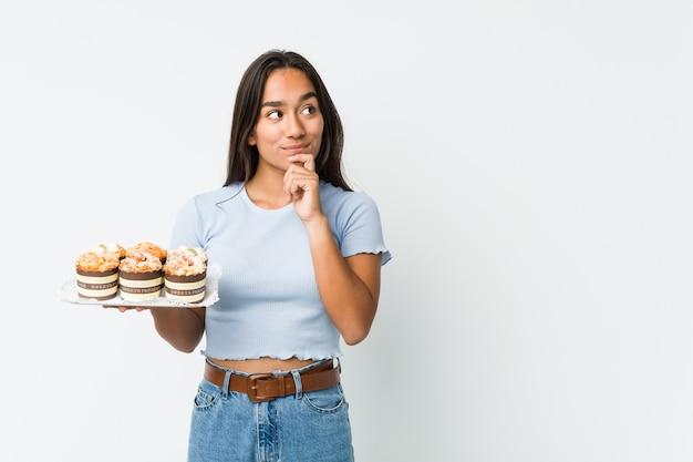 Młody indianin rasy mieszanej trzymający słodkie ciastka z wyrazem wątpliwości i sceptycyzmu.