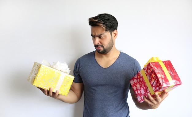 Młody indianin trzyma pudełko, boże narodzenie, walentynki, urodziny, koncepcja szczęścia
