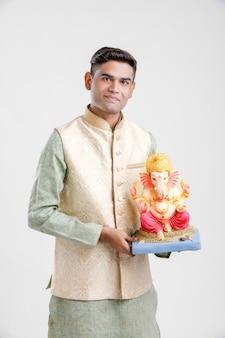 Młody indianin z lordem ganesha, świętujący festiwal ganesh