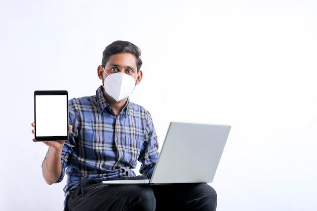 Młody indianin za pomocą laptopa i pokazując tablet na białym tle.