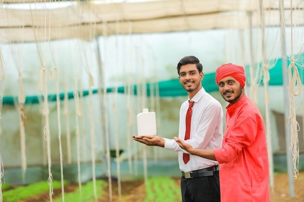Młody indyjski agronom i rolnik pokazując butelkę w szklarni