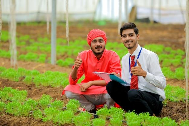 Młody indyjski agronom i rolnik pokazujący walenie w szklarnię lub polihouse