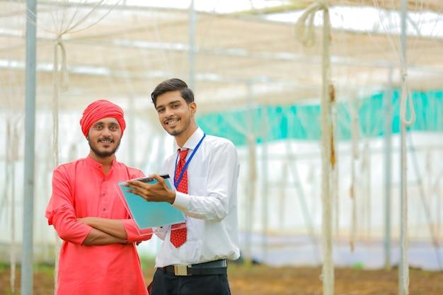 Młody indyjski agronom i rolnik rozmawiają w szklarni lub w polyhouse