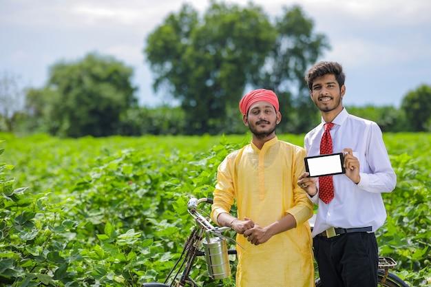 Młody indyjski agronom lub bankier pokazujący inteligentny telefon z rolnikiem na polu bawełny