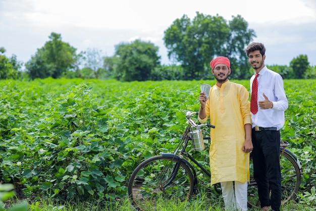 Młody indyjski agronom lub bankier z rolnikiem na polu.