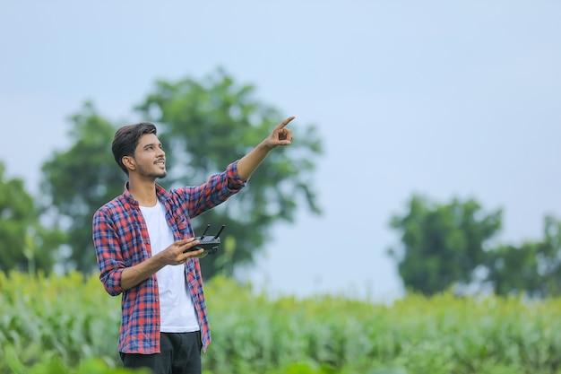 Młody indyjski agronom obsługuje lub kontroluje latające drony na polu rolniczym