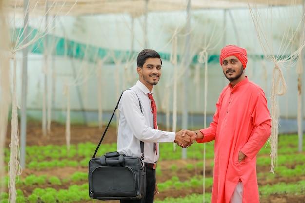 Młody indyjski agronom rozmawia z rolnikiem w szklarni