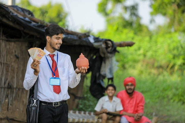 Młody indyjski bankier lub agronom pokazujący pieniądze i glinę skarbonkę trzymającą w ręku w domu biednego rolnika