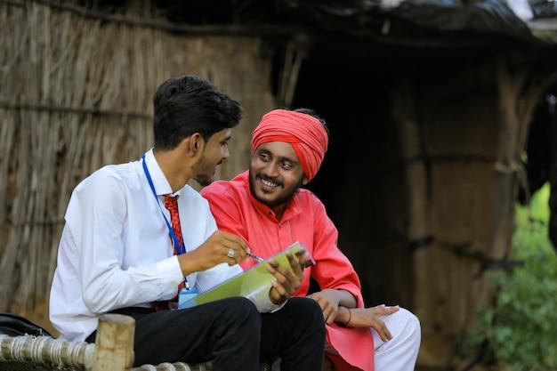 Młody indyjski bankier rozmawia z rolnikiem w domu
