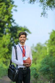 Młody indyjski bankier trzyma w ręku glinę skarbonkę