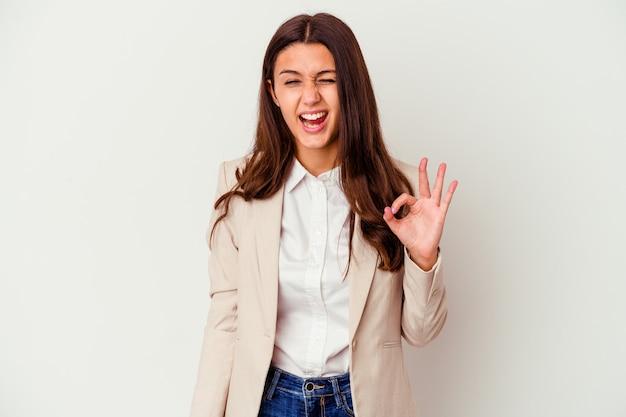 Młody indyjski biznes kobieta na białym mruga okiem i trzyma w porządku gest ręką.