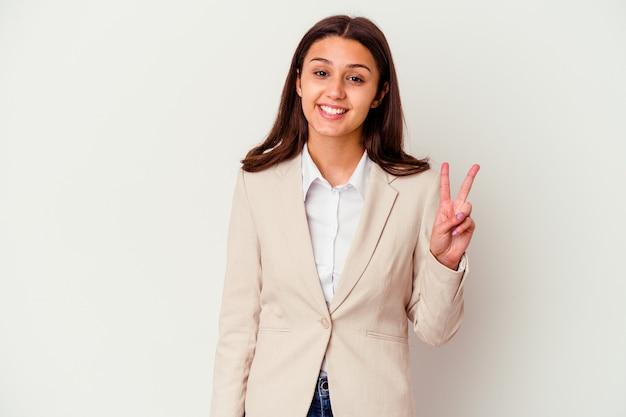 Młody indyjski biznes kobieta na białym tle na białej ścianie pokazując znak zwycięstwa i szeroko uśmiechając się.
