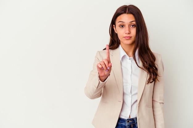 Młody indyjski biznes kobieta na białym tle na białej ścianie pokazuje numer jeden z palcem.
