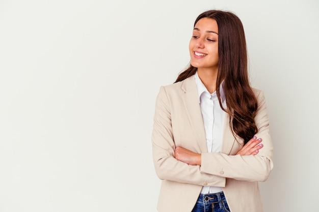 Młody indyjski biznes kobieta na białym tle na białej ścianie uśmiechnięty pewnie ze skrzyżowanymi rękami.