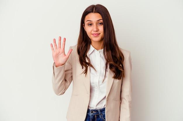 Młody indyjski biznes kobieta na białym tle na białej ścianie uśmiechnięty wesoły pokazując numer pięć palcami.