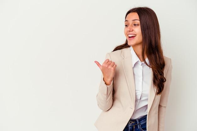 Młody indyjski biznes kobieta na białym tle na białej ścianie wskazuje z dala od kciuka, śmiejąc się i beztrosko.
