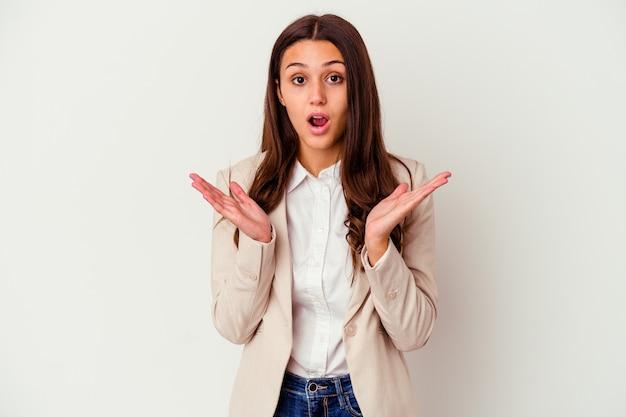 Młody indyjski biznes kobieta na białym tle na białej ścianie zaskoczony i zszokowany.
