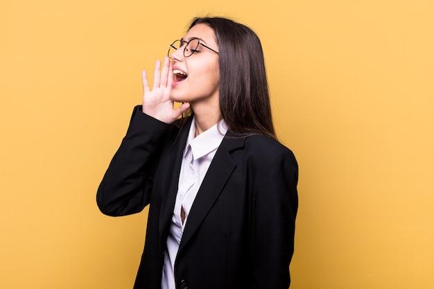 Młody indyjski biznes kobieta na białym tle na żółtej ścianie, krzycząc i trzymając dłoń w pobliżu otwartych ust.