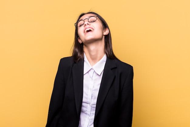 Młody indyjski biznes kobieta na białym tle na żółtej ścianie zrelaksowany i szczęśliwy, śmiejąc się, wyciągnięty szyję pokazując zęby.
