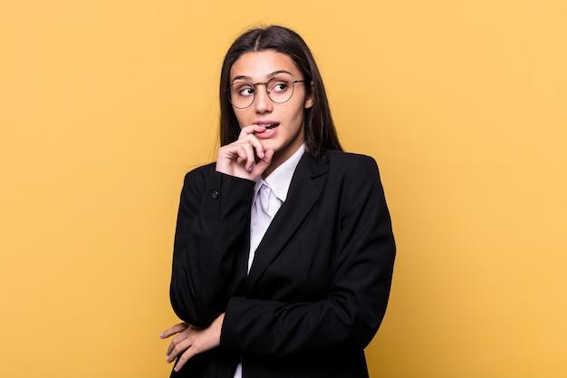 Młody indyjski biznes kobieta na białym tle na żółtej ścianie zrelaksowany myślenie o czymś patrząc na przestrzeń kopii.