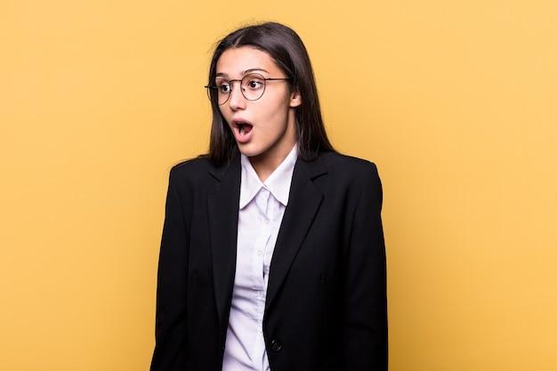 Młody indyjski biznes kobieta na białym tle na żółtym tle jest w szoku z powodu czegoś, co widziała.