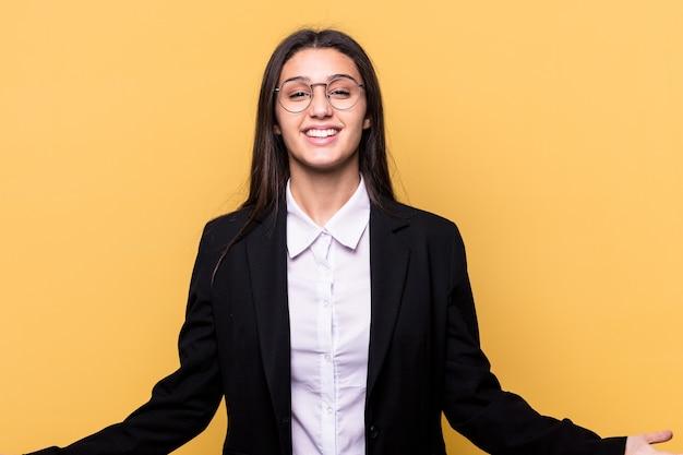 Młody indyjski biznes kobieta na białym tle na żółtym tle przedstawiający powitalny wyraz.