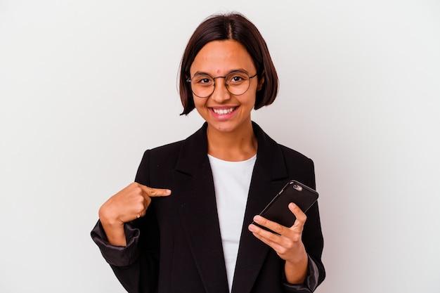 Młody indyjski biznes kobieta trzyma telefon na białym tle osoba, wskazując ręką na przestrzeni kopii koszuli, dumny i pewny siebie