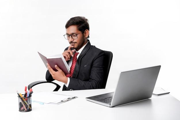 Młody indyjski biznesmen cheaking lub czytanie nabiału w biurze.