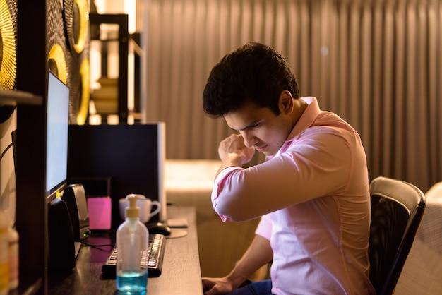 Młody indyjski biznesmen kaszle na rękawie podczas pracy w domu w godzinach nadliczbowych podczas kwarantanny