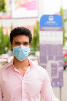 Młody indyjski biznesmen noszenie maski na przystanku autobusowym