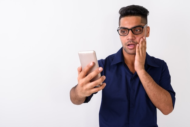 Młody indyjski biznesmen przy użyciu telefonu komórkowego na białym tle