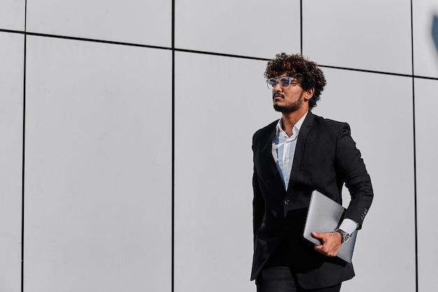 Młody indyjski biznesmen spacerujący z laptopem