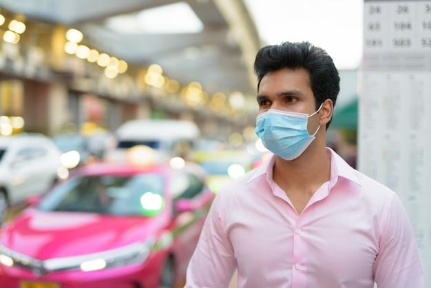 Młody indyjski biznesmen z maską czeka na przystanku autobusowym