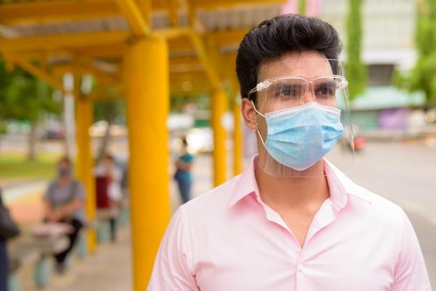 Młody indyjski biznesmen z maską i osłoną twarzy czeka na przystanku autobusowym