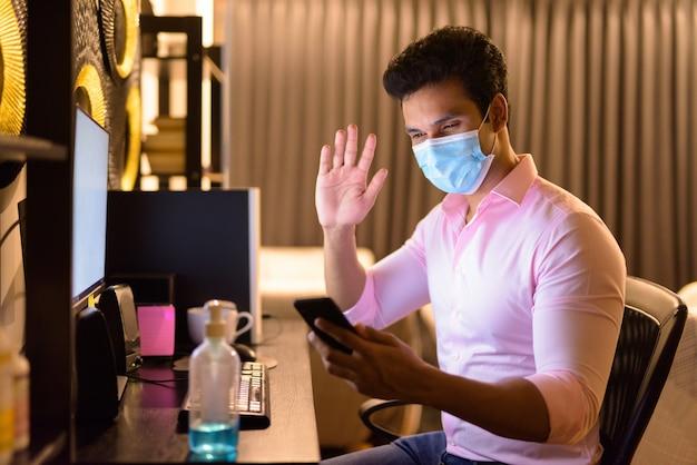 Młody indyjski biznesmen z maską, rozmowy wideo za pomocą telefonu podczas pracy w nadgodzinach w domu podczas kwarantanny
