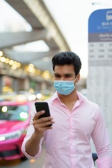 Młody indyjski biznesmen z maską za pomocą telefonu na przystanku autobusowym