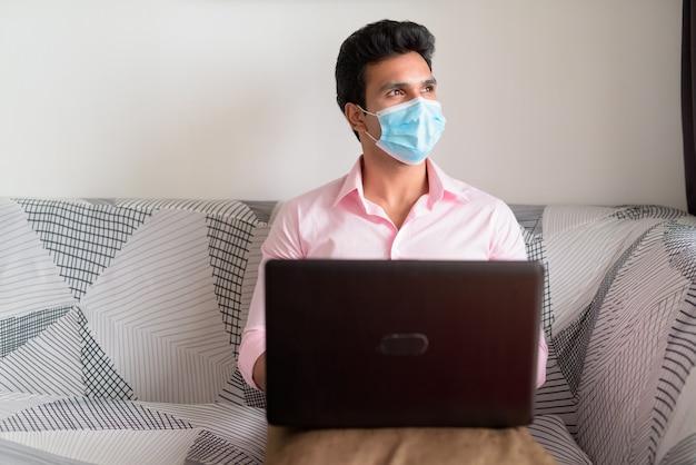 Młody indyjski biznesmen z myśleniem maski podczas korzystania z laptopa i przebywania w domu w ramach kwarantanny