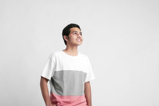 Młody indyjski chłopiec pokazując wyrażenie na białej ścianie