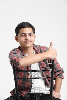 Młody indyjski chłopiec siedzi na krześle i pokazuje wyrażenie na białej ścianie