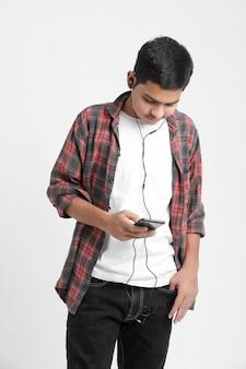 Młody indyjski chłopiec słuchanie muzyki i używanie smartfona na białej ścianie