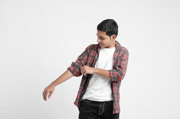 Młody indyjski chłopiec w swobodnym stroju i pokazujący wyraz na białej ścianie